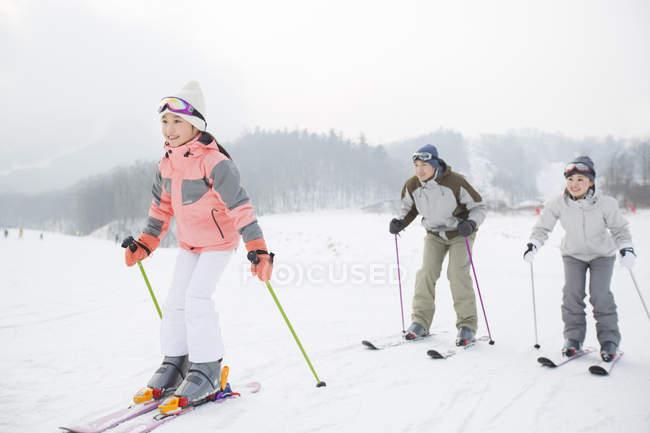 Китайская семья с дочерью, Катание на лыжах в горнолыжном курорте — стоковое фото