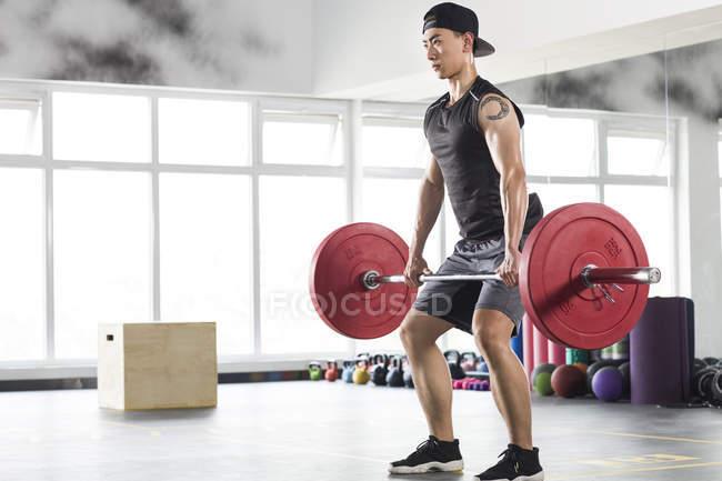 Asiatischer Mann Aufhebung Hanteln im Fitnessstudio — Stockfoto
