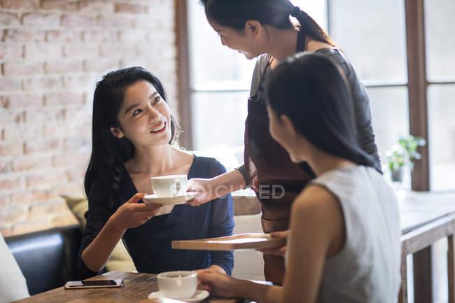 Китайская официантка, подающая кофе подружкам в кафе — стоковое фото
