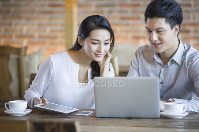 Chinese man and woman using laptop together in cafe — Stock Photo
