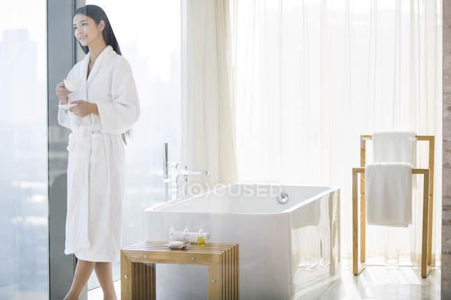 Женщина в халате, держа кофе и смотреть через окно ванной — стоковое фото