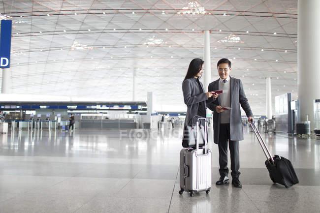 Asiático hombre y mujer mirando los pasaportes en el vestíbulo del aeropuerto - foto de stock
