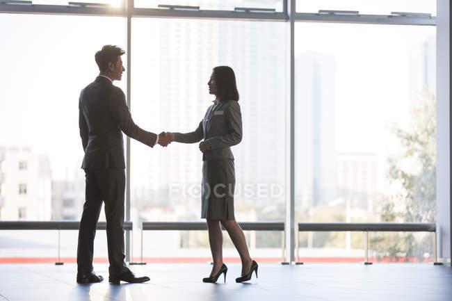 Chinesische Geschäftsleute beim Händeschütteln im Bürogebäude — Stockfoto