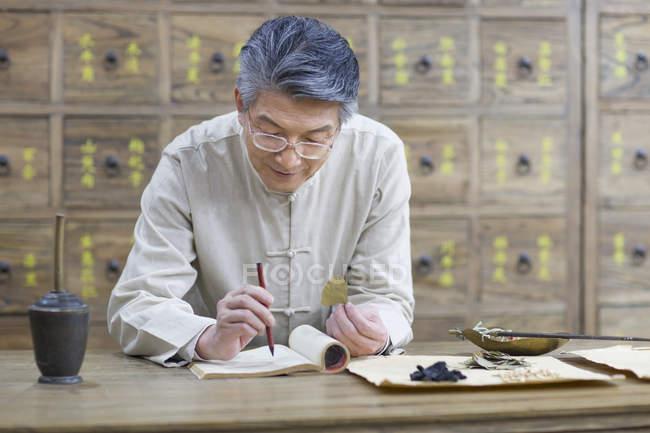 Mature médecin chinois examinant les herbes médicinales — Photo de stock