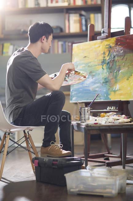 Asiatischer männlicher Maler arbeitet im Kunstatelier — Stockfoto