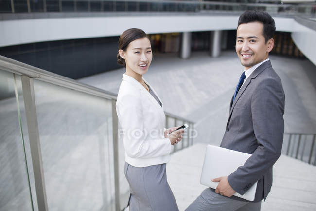 Asian business people standing on street with gadgets and smiling — Stock Photo