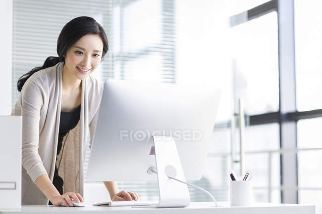Smiling chinese woman using computer in office — Stock Photo