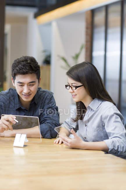 Chinês-trabalhadores desenvolvendo tablet digital no escritório — Fotografia de Stock