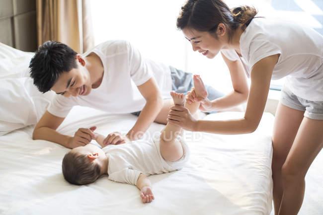 Cinese madre holding bambino ragazzo gambe su letto con padre — Foto stock
