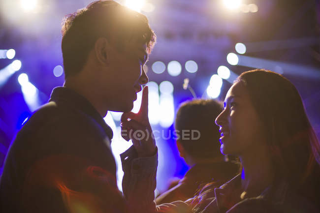 Chinese woman putting finger on male lips at music festival — Stock Photo
