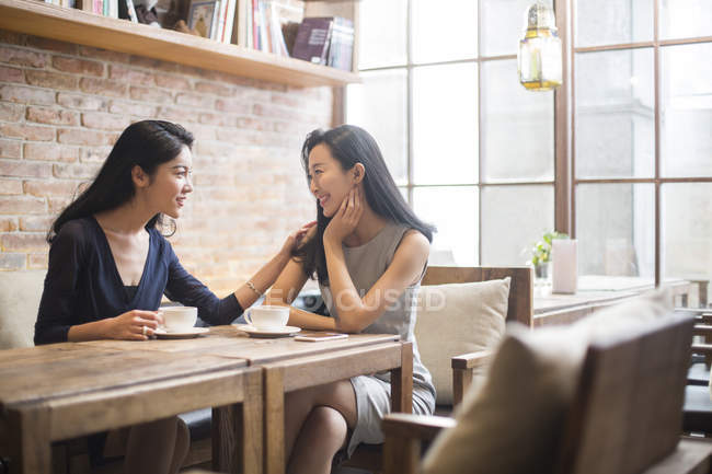 Chinese female friends talking with coffee cups in cafe — Stock Photo