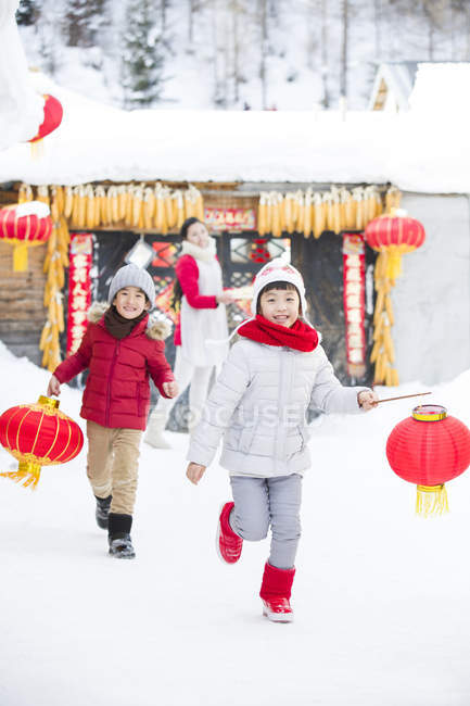 Children running with Chinese lanterns with mother in background — Stock Photo