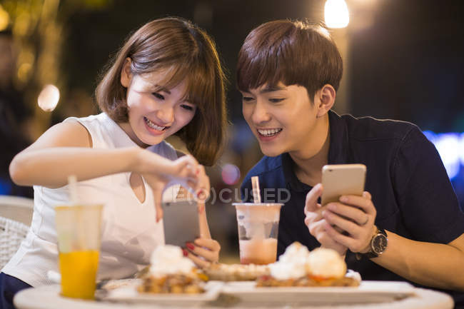 Young Chinese couple taking picture of dessert in cafe — Stock Photo