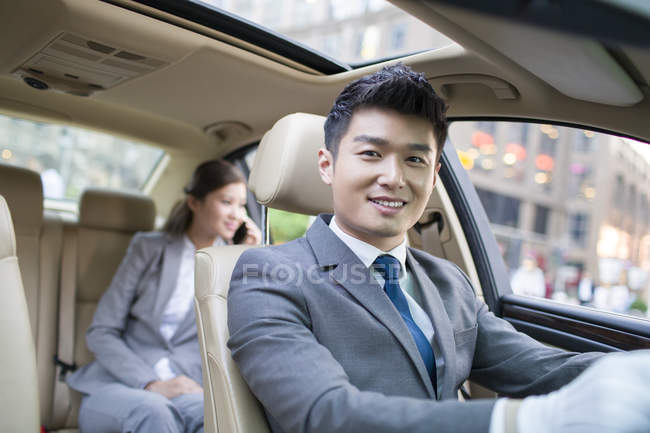 Chinese chauffeur driving car with businesswoman talking on phone on back seat — Stock Photo