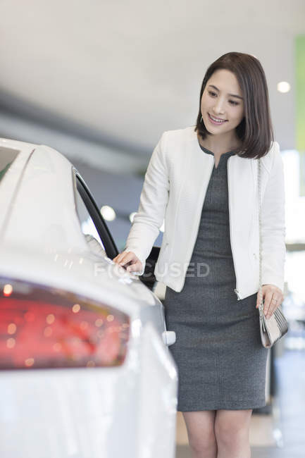 Chinese woman choosing car in showroom — Stock Photo