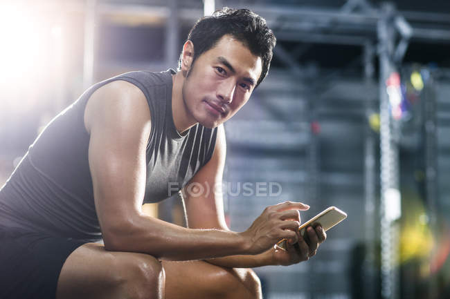 Chinese man using smartphone in gym — Stock Photo