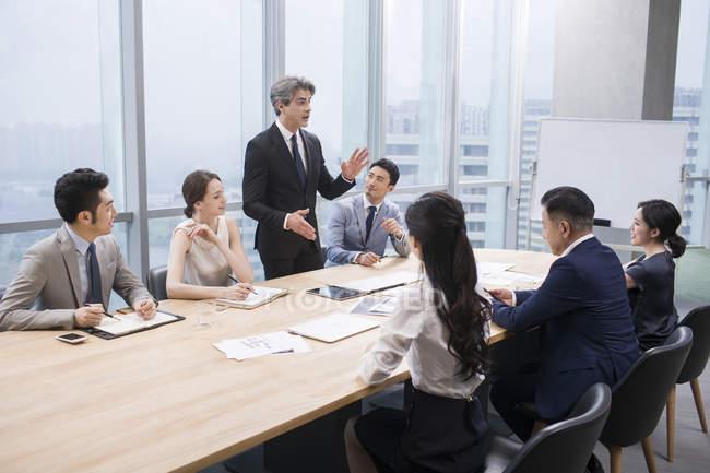 Team d'affari cinese che si incontra con partner stranieri in sala riunioni — Foto stock