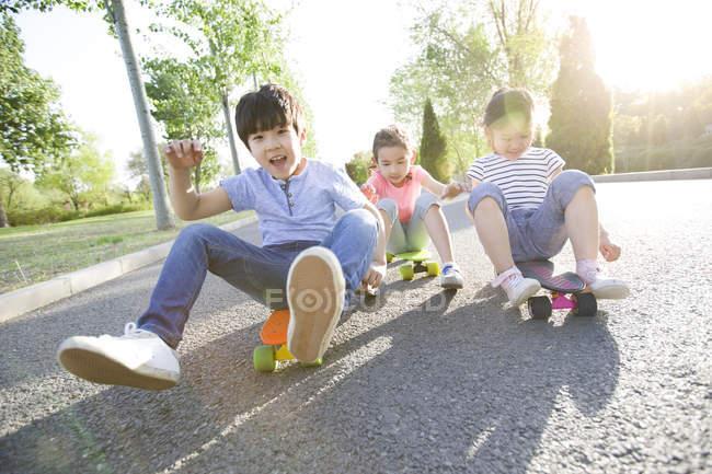 Enfants chinois assis alors qu'il circulait sur planches à roulettes — Photo de stock