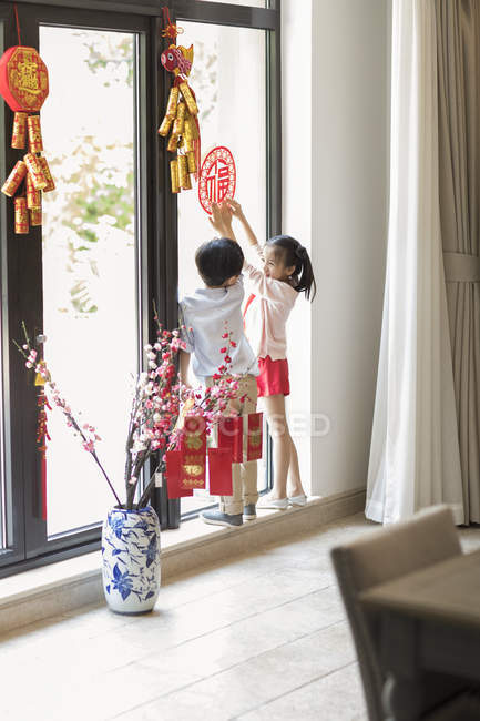 Children decorating window with Chinese New Year paper-cut — Stock Photo
