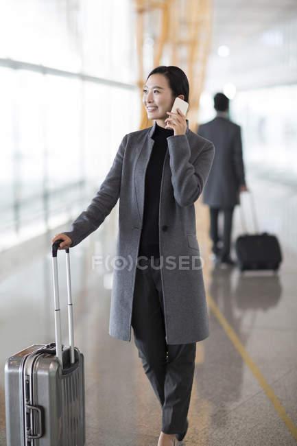Mujer asiática hablando por teléfono en el aeropuerto - foto de stock