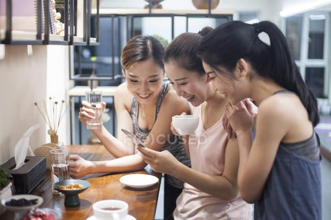 Amigos femeninos usando smartphone mientras beben café en la cocina - foto de stock