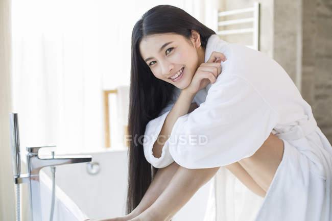 Китаянка сидит в ванной комнате в Халат — стоковое фото