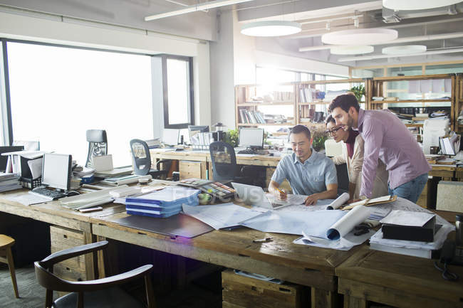 Architects working in office interior with laptop — Stock Photo