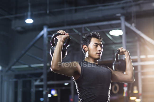Chinesischer Mann Training mit Kettlebells in Crossfit gym — Stockfoto