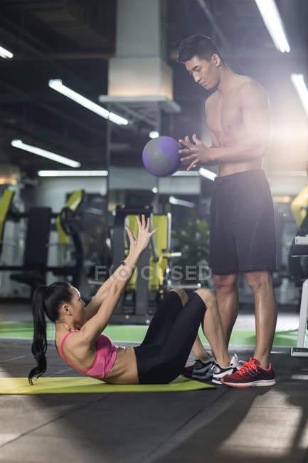 Китаянка работает с тренером и мячом в спортзале — стоковое фото