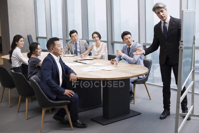 Businessman showing presentation at meeting in board room — Stock Photo