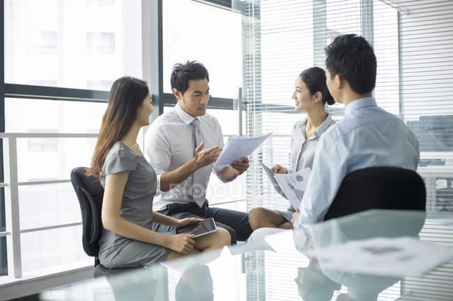 Équipe d'affaires chinoise discutant du travail en réunion — Photo de stock