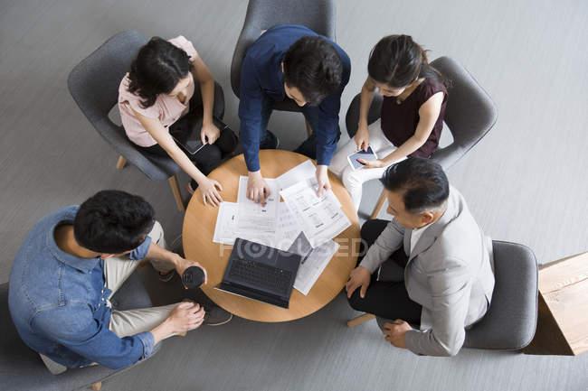 Китайський ділових людей говорити в зустрічі з ноутбуком, вигляд згори — стокове фото