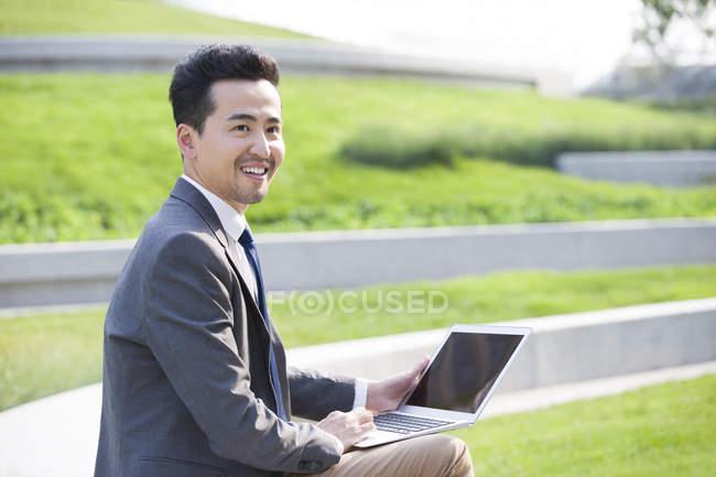Asiatico uomo d'affari utilizzando laptop all'aperto — Foto stock