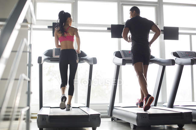 Chinese couple exercising on treadmills in gym — Stock Photo