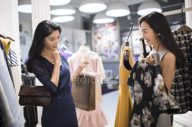 Chinese female friends choosing between dresses in clothing store — Stock Photo