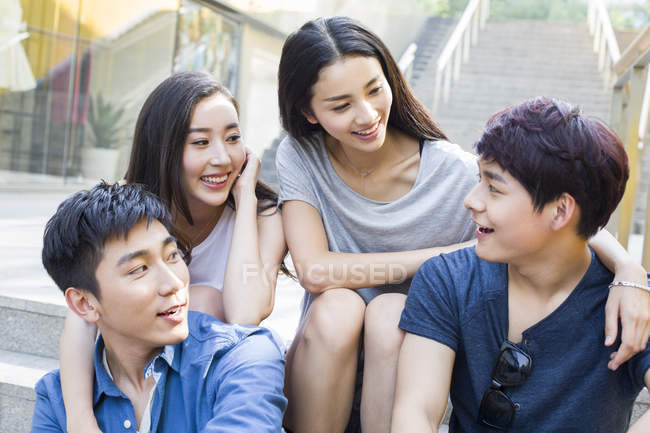 Chinese friends talking together on stairs — Stock Photo