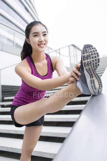 Donna cinese allungamento gamba in strada — Foto stock