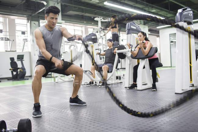 Homme asiatique avec luttant contre la corde au gymnase — Photo de stock