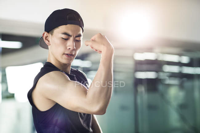 Asian man in sports clothing flexing muscles — Stock Photo