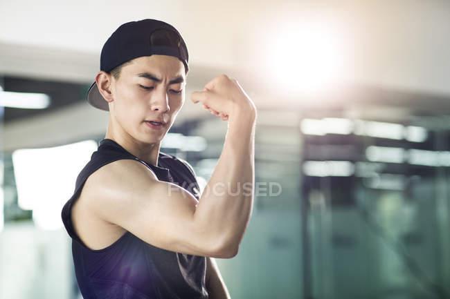 Asiatischer Mann in Sportbekleidung biegen Muskeln — Stockfoto