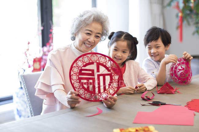 Внуки и бабушка с китайской новогодней вырезкой из бумаги — стоковое фото