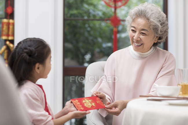Chinese grandmother giving red envelope to granddaughter — Stock Photo