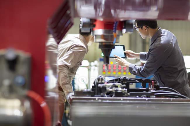 Китайские инженеры используют цифровой планшет на заводе — стоковое фото