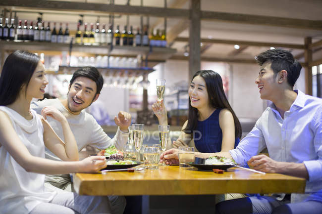 Asian friends having dinner together in restaurant — Stock Photo