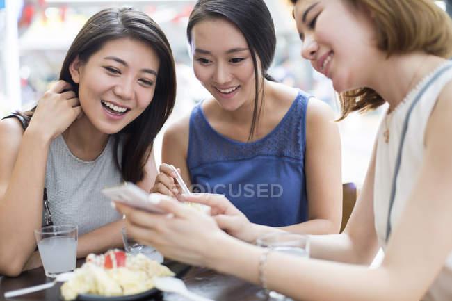 Жіночий друзів за допомогою смартфона на тротуарі кафе — стокове фото