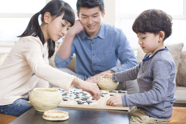 Asian man watching children playing Go game at home — Stock Photo