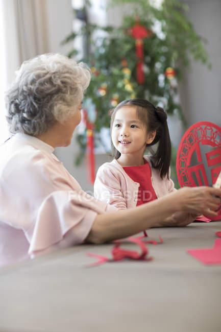Внучка и бабушка делает китайский Новый год-вырезки — стоковое фото