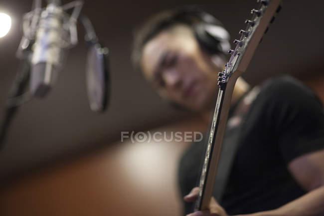 Chinese man playing guitar in recording studio — Stock Photo