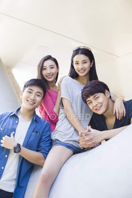 Chinese friends sitting in building and looking in camera — Stock Photo