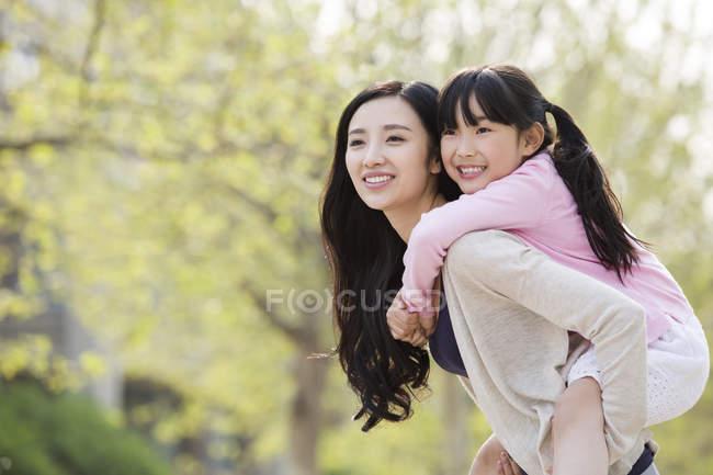 Asiatische Mutter Reiten Tochter huckepack in Park — Stockfoto